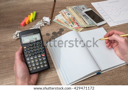 financial concept - blank notepad, calculator, pen and smartphone on the table