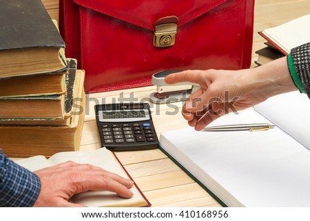 Financial concept. Business partners discuss profit and losses, analyzing financial results. On a wooden table books, documents, calculator, stapler, red briefcase.