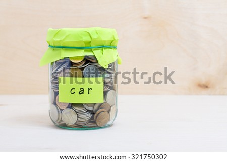 Financial concept. Coins in glass money jar with car label. Wooden background - stock photo