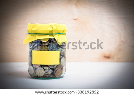 Financial concept. Coins in glass money jar with label. Wooden background - stock photo