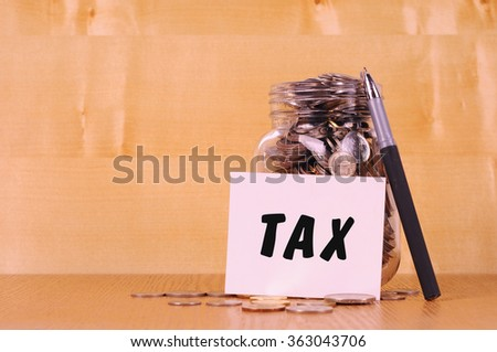 Financial concept. Coins in glass money jar with tax label. Wooden background - stock photo