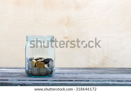 Financial concept. Coins in glass money jar. Wooden background - stock photo