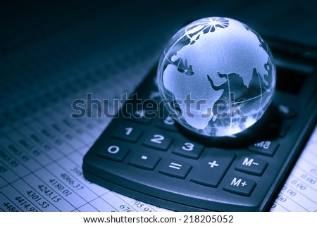 Financial concept. Glass globe on calculator on background with table of numbers