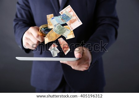 Financial concept. Make money on the Internet. Businessman holding magnifying glass and digital tablet on dark grey background - stock photo