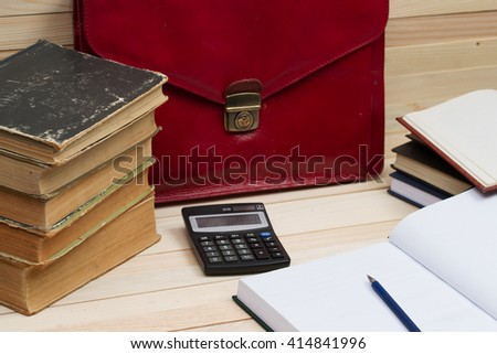 Financial concept. On a wooden table books, documents, calculator, red briefcase. Copy space