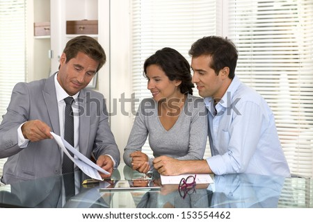 Financial consultant presenting a business investment to a smiling young couple, indoor - stock photo