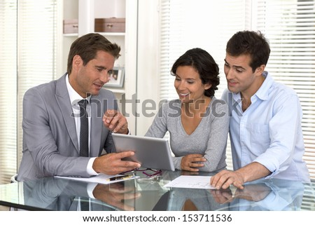 Financial consultant presenting a new project investment to a smiling young couple - stock photo
