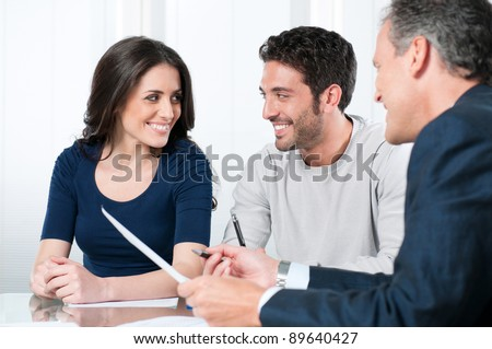 Financial consultant presents bank investments to a young couple - stock photo
