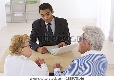 Financial consultant presents bank investments to an elderly couple - stock photo