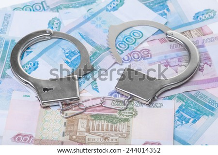 financial crime. Steel handcuffs and money, closeup - stock photo