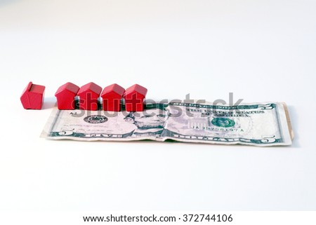 Financial crisis and housing market. Tiny wooden houses and dollar banknotes - stock photo