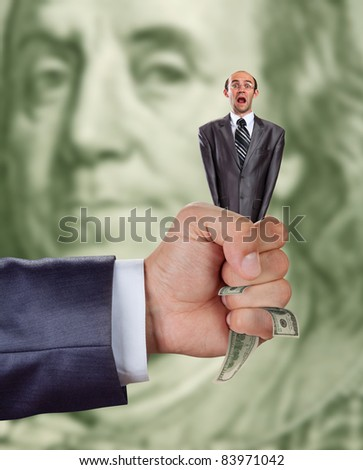 financial crisis concept - hand squeezing businessman full of money - stock photo