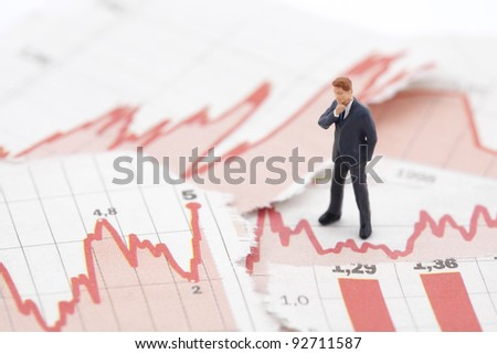 Financial crisis. Figure of businessman on financial charts