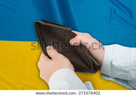 Financial Crisis in Ukraine - Man's Hand With Empty Wallet and Ukrainian  flag - stock photo