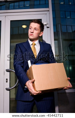 Financial crisis. Unemployed young manager leaving business center in megalopolis - stock photo