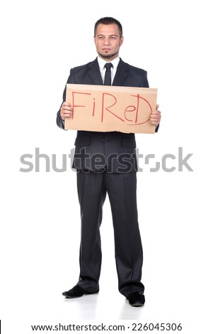 Financial crisis. Unemployment. Young businessman with sign Fired isolated on white. - stock photo