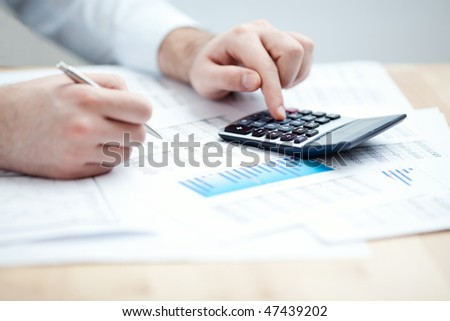 Financial data analyzing. Counting on calculator. Close-up. Selective focus
