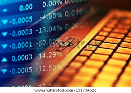 Financial data on a monitor and notebook. Finance data concept. - stock photo