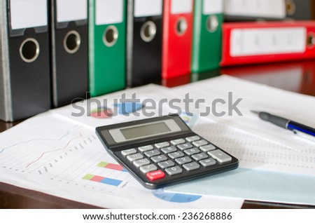 Financial documents with calculator and pen - stock photo