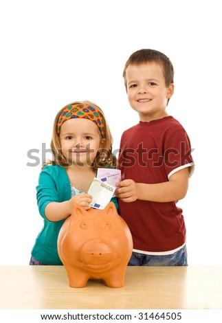 Financial education and discipline concept - kids feeding their piggy bank - stock photo