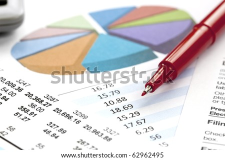 Financial figures, pie chart, and red felt pen.  Shallow depth of field. - stock photo