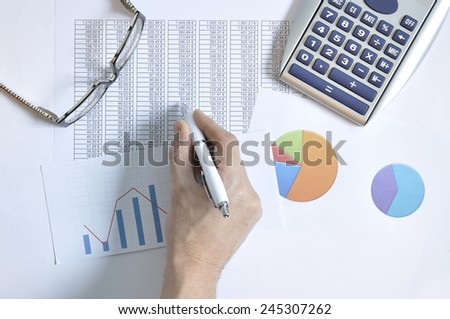 Financial graphs and business report with a calculator, glasses and the hand of a man taking notes - stock photo