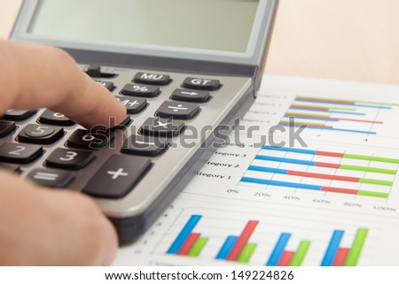 Financial graphs and charts with calculator - stock photo