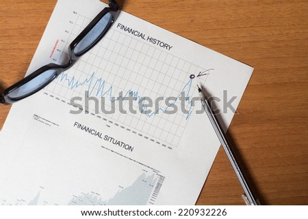 Financial history report on the desktop with glasses and pen - stock photo
