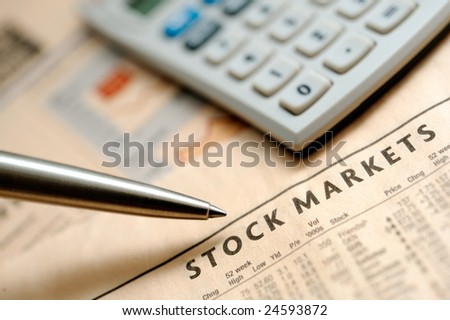Financial newspaper and calculator - stock photo