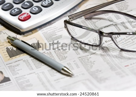 financial newspaper with eye glasses and calculator - stock photo