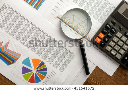 Financial paper charts and graphs on the table. - stock photo