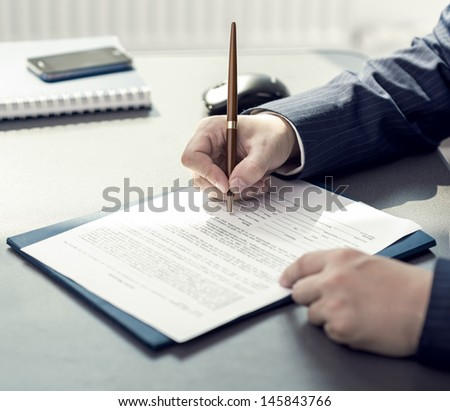 Financial planning specialist signing annual report in company's office. Businessman sitting at the desk with accounting papers and ballpoint.  - stock photo