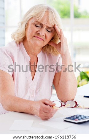 Financial problems. Frustrated senior woman leaning her head on hand and keeping eyes closed while sitting at the table with bills and calculator on it