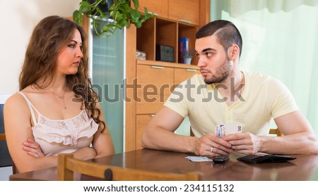 Financial problems in family. Sad couple calculating budget at the table  - stock photo