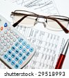 Financial report - calculator, glasses, pen and papers - stock photo