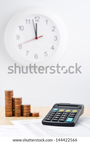 Financial report. Descending money stacks next a calculator with business reports - stock photo