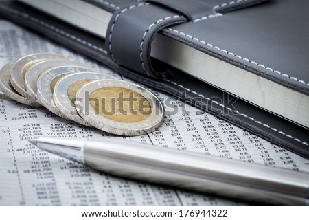 financial report with coins and pen