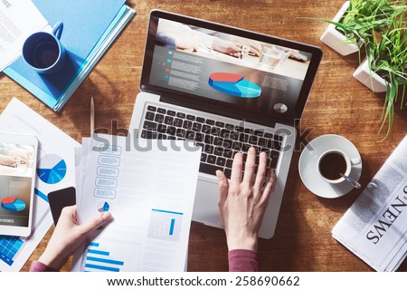 Financial report with pie chart and data on a laptop with business woman's hands at work - stock photo