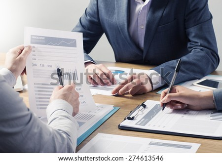 Financial service professional team at work, hands close with business reports and paperwork - stock photo