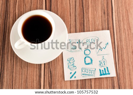 Financial signs on a napkin and cup of coffee - stock photo
