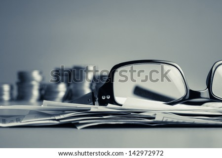 Financial work on the desk in cold tone color (eyeglasses, bills, and coins) - stock photo