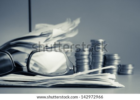 Financial work on the desk in cold tone color (eyeglasses, bills, paper nail and coins) - stock photo