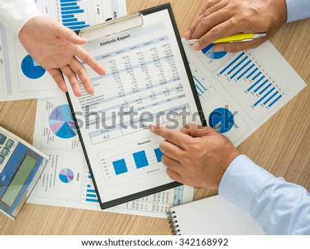 financial worker analyzing statistical data on desk in office. top view - stock photo