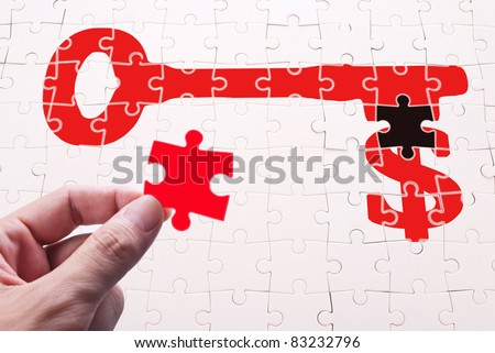 Find key of wealth, human hand and puzzle game. - stock photo