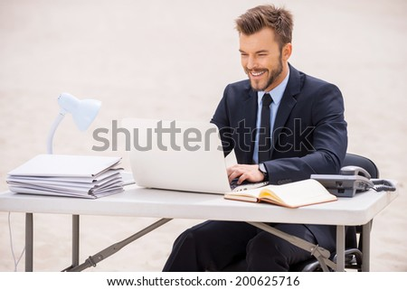 Finding a peaceful place to work. Cheerful young man in formalwear working on laptop while sitting at the table on sand - stock photo
