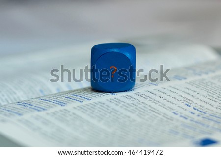 Finding an answer - blue cube with a question mark on the page of a dictionary