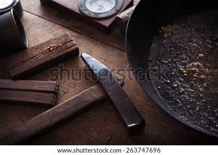 Finding gold. gold panning, digging or gold prospecting. Gold on wash pan with Gold prospecting tools. - stock photo