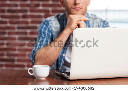 Finding out solution. Close-up of young man sitting at the table with laptop on it  - stock photo