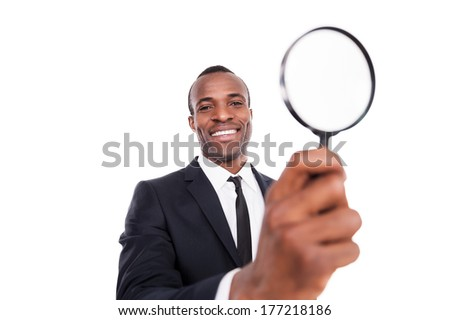 Finding out the truth. Low angle view of cheerful young African man in formalwear holding a magnifying glass and smiling while standing isolated on white background  - stock photo