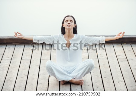Finding peace and balance. Beautiful young woman in white clothing sitting in lotus position and keeping eyes closed while meditating outdoors - stock photo